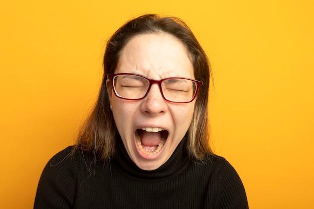 Молодая красивая девушка в черной водолазке и очках кричит с раздраженным выражением лица