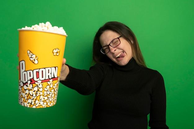 Молодая красивая девушка в черной водолазке и очках показывает ведро с попкорном, счастливая и возбужденная, высунув язык