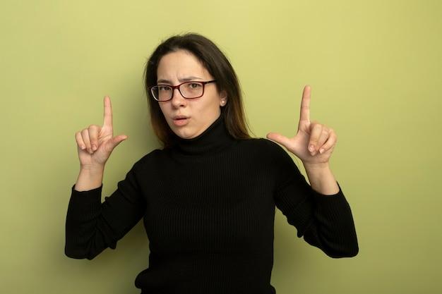 Молодая красивая девушка в черной водолазке и очках показывает указательные пальцы с серьезным выражением лица