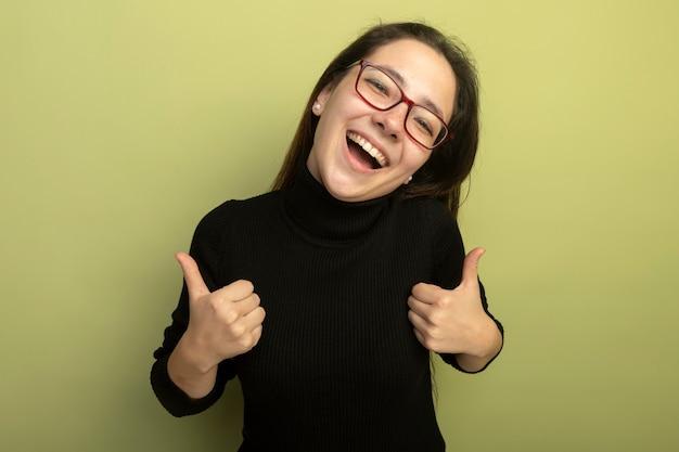 親指を立てて幸せそうな顔で笑って黒いタートルネックとメガネの若い美しい少女