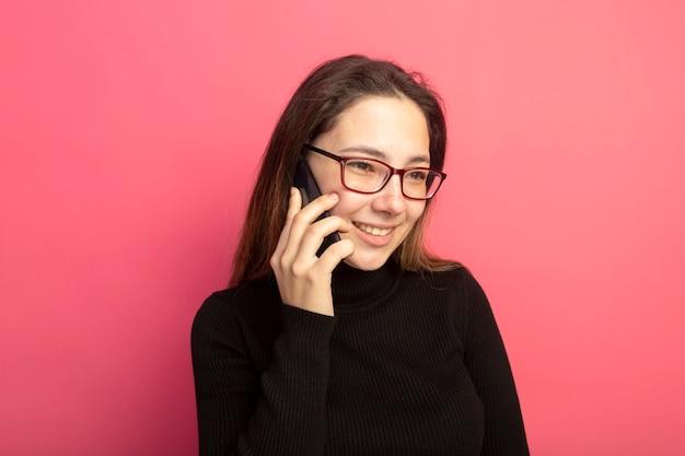 검은 터틀넥과 안경에 젊은 아름다운 소녀가 행복한 얼굴로 웃고 휴대 전화에 이야기