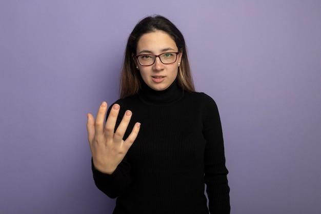 Молодая красивая девушка в черной водолазке и очках с вытянутой рукой недовольна Бесплатные Фотографии