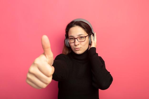 Молодая красивая девушка в черной водолазке и очках с наушниками с улыбкой на лице показывает палец вверх