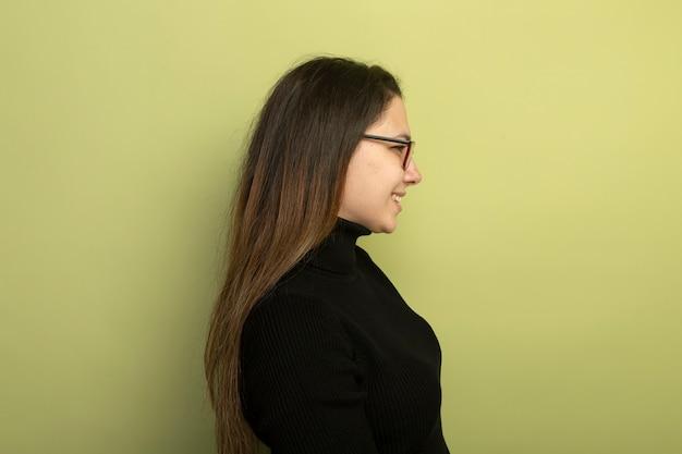 Молодая красивая девушка в черной водолазке и очках