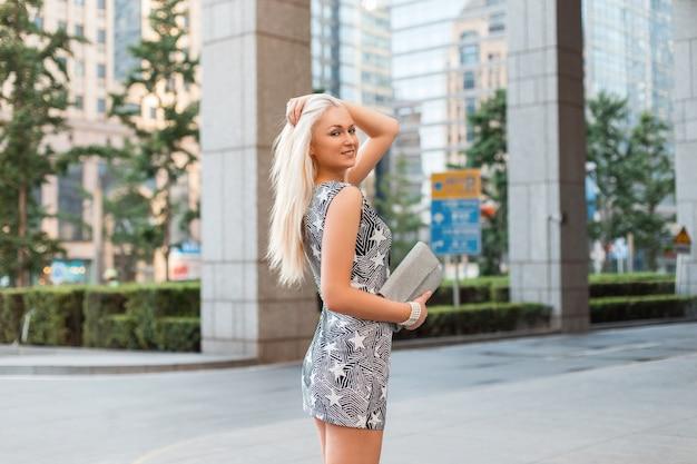 ハンドバッグを保持しているドレスの若い美しい少女