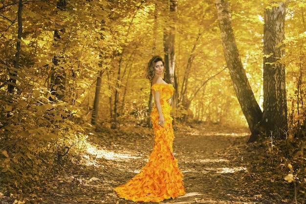 Молодая красивая девушка в платье из осенних листьев в парке в осенний сезон. художественная фотография.