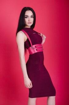 革のポートで若い、美しい女の子。女の子の服にセクシーな革のアクセサリー。衣類アクセサリーとしての革ベルト