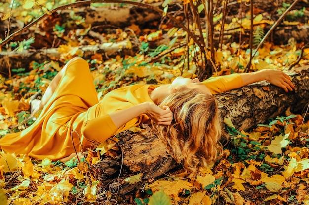 秋の公園の地面に横たわっている長い黄色のドレスを着た若い美しい少女
