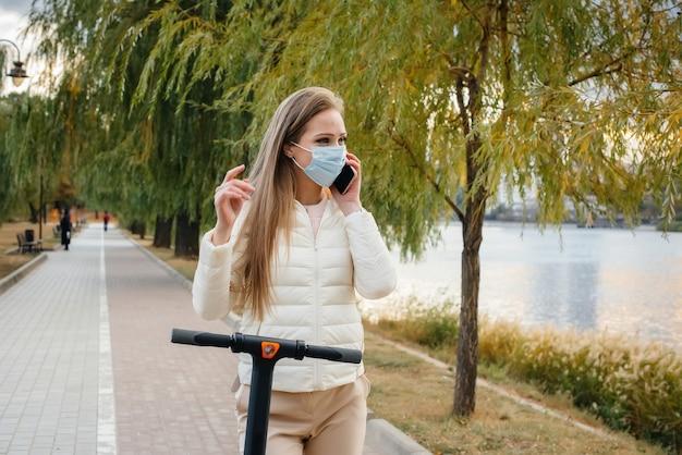 Молодая красивая девушка в маске катается в парке на электросамокате в теплый осенний день и разговаривает по телефону. гулять в парке.