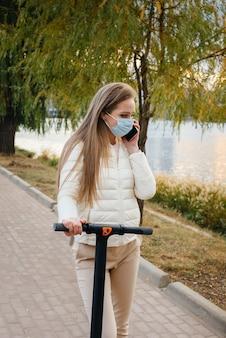 따뜻한 가을 날에 전기 스쿠터를 타고 공원에 타고 전화로 이야기하는 마스크의 젊은 아름다운 소녀