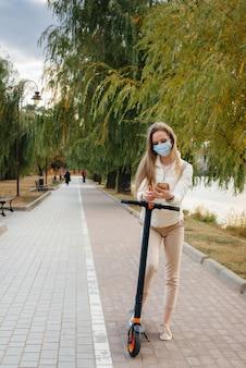 Молодая красивая девушка в маске катается в парке на электросамокате в теплый осенний день и разговаривает по телефону