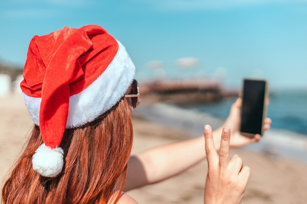 赤いサンタクロースの帽子と水着を着た若い美しい少女が海岸で自分撮りをします
