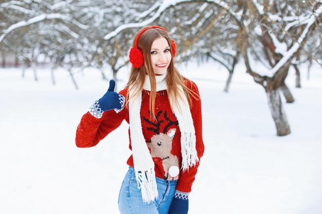 公園で楽しむためにトナカイと冬のヘッドフォンと赤いセーターを着た若い美しい少女