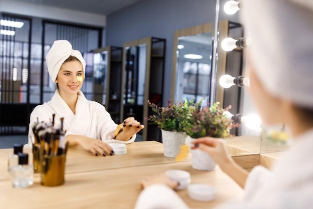 하얀 목욕 가운을 입고 머리에 수건을 두른 어린 소녀는 거울 앞에서 눈 밑에 패치를 붙입니다