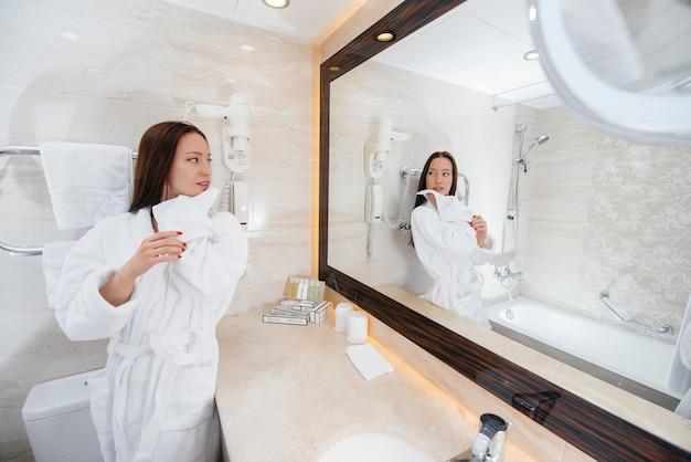 Молодая красивая девушка в белой красивой ванной комнате. свежее доброе утро в отеле.