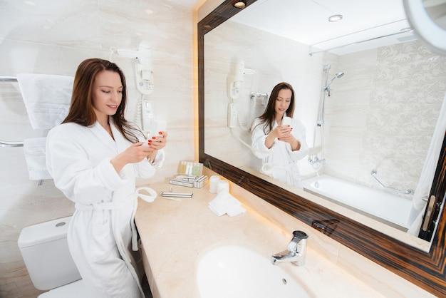 Молодая красивая девушка в белой красивой ванной комнате разговаривает по телефону. свежее доброе утро в отеле.