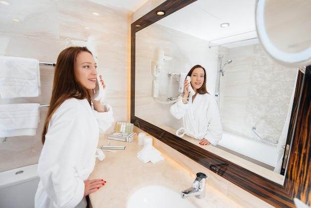 Молодая красивая девушка в белой красивой ванной комнате разговаривает по телефону