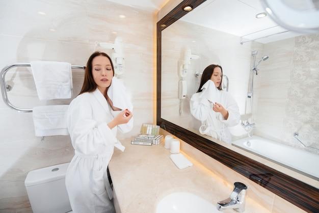 Молодая красивая девушка в белой красивой ванной комнате