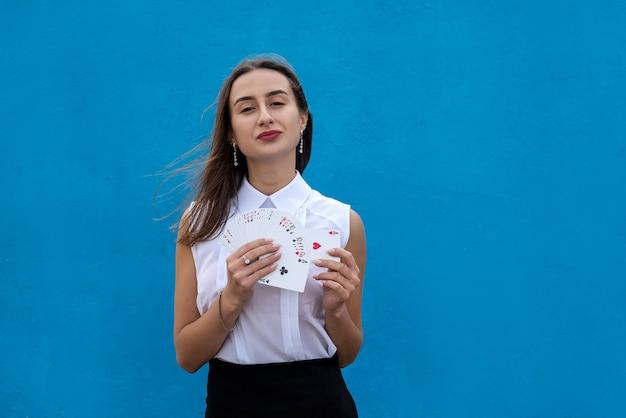 흰 블라우스를 입은 아름다운 소녀가 파란 벽에 포커 카드 놀이를 하고 있다