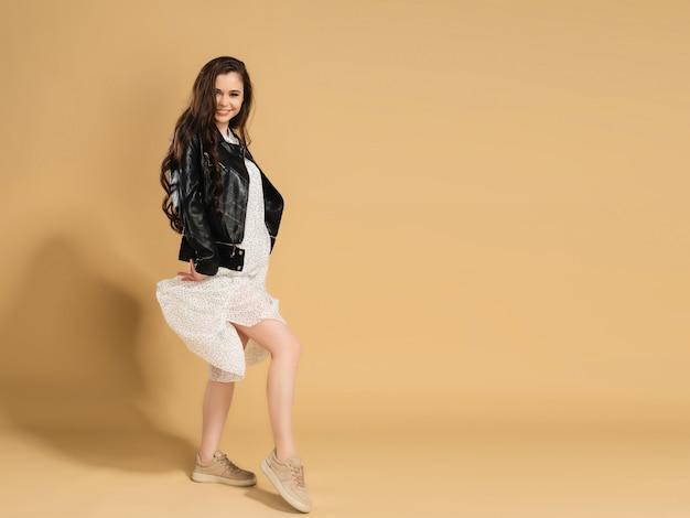 水玉模様の白いドレスと黒い革のジャケットを着た若い美しい少女は、パステルオレンジで彼女のドレスの裾を持ち上げます。