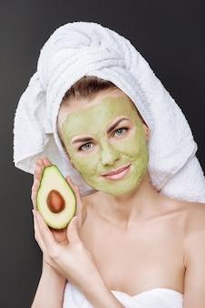 Молодая красивая девушка в белом полотенце на голове с косметической маской из авокадо на лице.