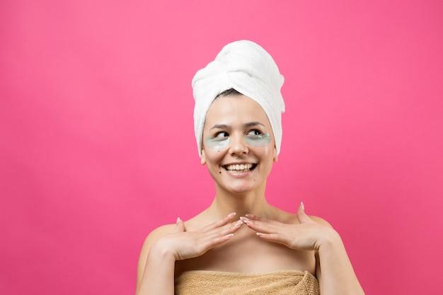 Молодая красивая девушка в белом полотенце на голове носит пластыри из коллагенового геля под глазами. маска под глаза для ухода за лицом.