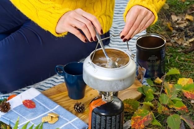 黄色いセーターを着た若い美しい少女は、ガスバーナーで森の中でコーヒーを作ります。秋の森のプリムスストーブでコーヒーを作る