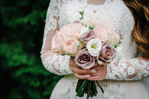 우아한 드레스에 젊은 아름 다운 소녀 서 꽃의 꽃다발을 들고