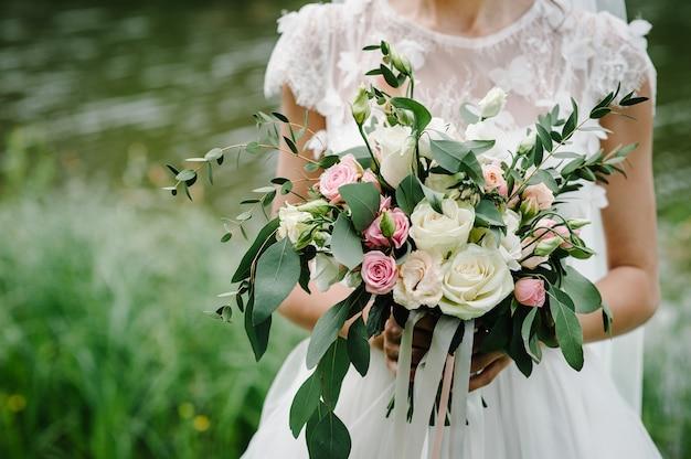 Молодая красивая девушка в элегантном платье стоит и держит в руке букет