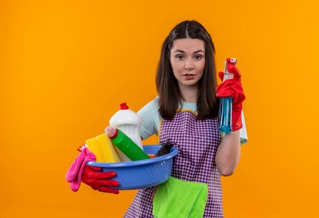 掃除道具と掃除スプレーで洗面器を保持しているエプロンとゴム手袋の若い美しい女の子は自信を持って見え、掃除の準備ができています