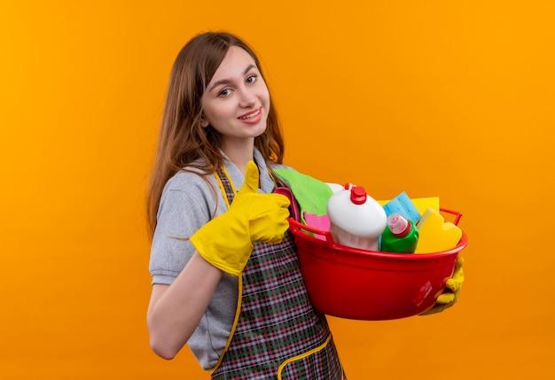 エプロンとゴム手袋で洗面器を保持している若い美しい少女は、元気に親指を見せて笑っているクリーニングツール