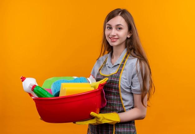 エプロンとゴム手袋で洗面器を保持している若い美しい少女は元気に笑って掃除道具を持っています