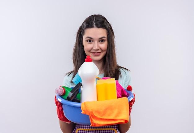 自信を持って笑っているクリーニングツールと洗面器を保持しているエプロンとゴム手袋の若い美しい少女