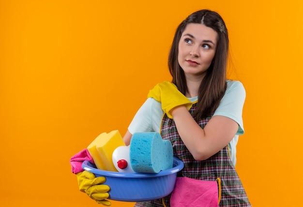 Молодая красивая девушка в фартуке и резиновых перчатках держит таз с чистящими средствами, касаясь плеча, чувствуя боль