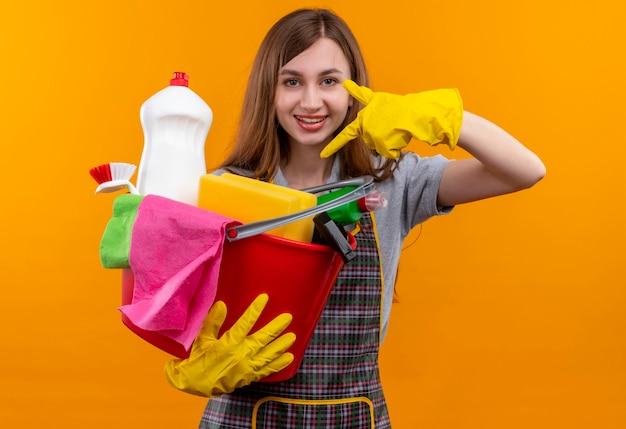 エプロンとゴム手袋の若い美しい女の子は、元気に笑ってそれに指で指しているクリーニングツールでバケツを保持しています