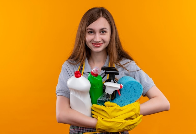 Молодая красивая девушка в фартуке и резиновых перчатках, весело улыбаясь, держит в руках принадлежности и инструменты для очистки