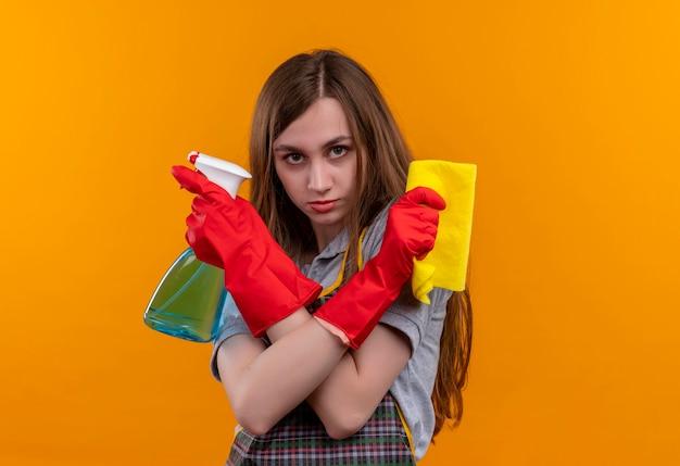 エプロンとゴム手袋の若い美しい少女は、真面目な顔で防衛ジェスチャーを作るクレニングスプレーと敷物の交差する手を保持しています
