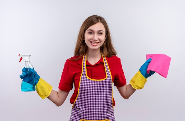 エプロンとゴム手袋の若い美しい少女は、元気に笑顔でカメラを見ているクリーニングスプレーと敷物を保持し、wjiteの背景を掃除する準備ができています