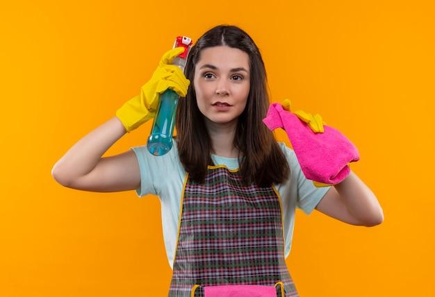 自信を持って見えるクリーニングスプレーと敷物を保持しているエプロンとゴム手袋の若い美しい少女