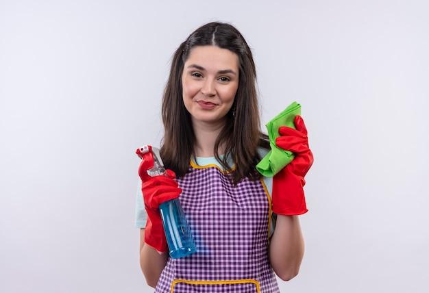 エプロンとゴム手袋の若い美しい少女は、自信を持って笑顔、掃除の準備ができて、クリーニングスプレーと敷物を保持しています