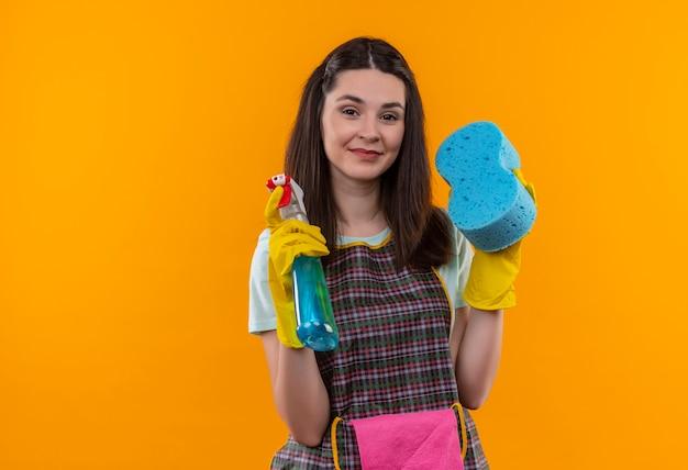 自信を持って笑顔のカメラを見てクリーニングスプレーとスポンジを保持しているエプロンとゴム手袋の若い美しい少女