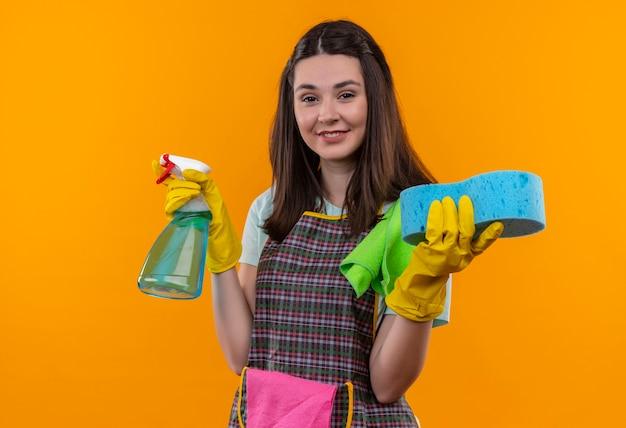 エプロンとゴム手袋の若い美しい少女は、幸せそうな顔で笑顔のカメラを見てクリーニングスプレーとスポンジを保持しています。