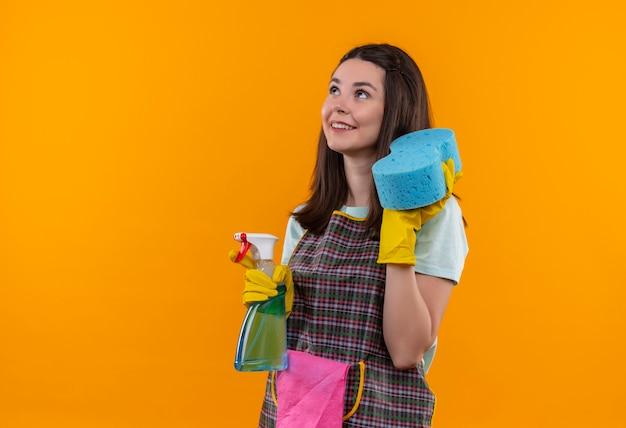 Молодая красивая девушка в фартуке и резиновых перчатках держит чистящий спрей и губку, уверенно улыбаясь