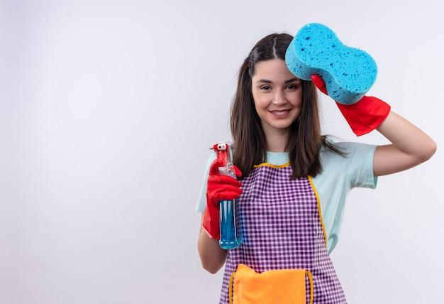 エプロンとゴム手袋をはめて、元気に笑っているスポンジを示すクリーニングスプレーを保持している若い美しい少女
