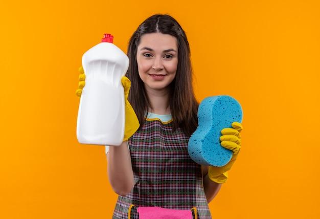 自信を持って笑顔のカメラを見てクリーニング用品とスポンジを保持しているエプロンとゴム手袋の若い美しい少女