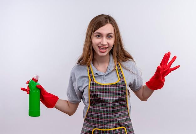 Молодая красивая девушка в фартуке и резиновых перчатках держит чистящие средства, весело улыбаясь