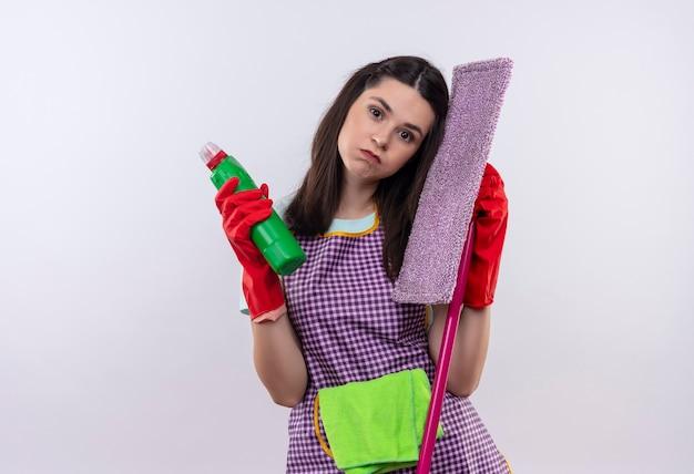 エプロンとゴム手袋をはめて、掃除用品とモップを持った若い美しい少女は、顔に悲しい表情で疲れて過労に見えます
