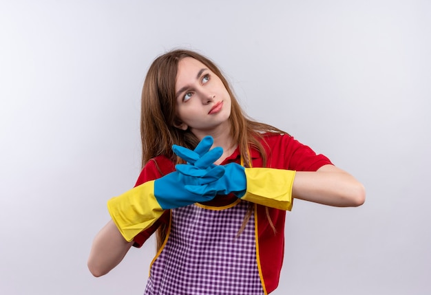 物思いにふける表情で脇を見ながら手をつないでエプロンとゴム手袋の若い美しい少女