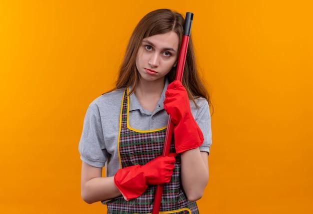Молодая красивая девушка в фартуке и резиновых перчатках держит швабру, опираясь на нее головой, смотрит в камеру с грустным выражением лица