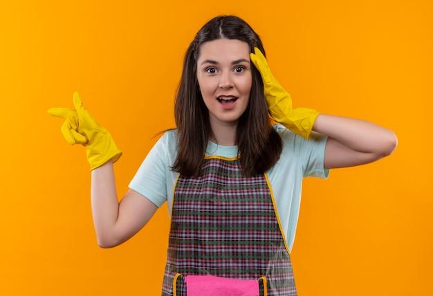 エプロンとゴム手袋の若い美しい少女は、横に指で指して驚いて驚いて見える